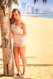 Blonde girl in lace holds palm trunk smiles on beach Royalty Free Stock Photos