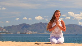 blonde girl in lace maditates in yoga asana sits on knees stock video