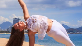 blonde girl in lace shows yoga asana half moon on beach stock video footage