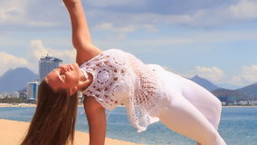 blonde girl in lace shows yoga asana half moon on beach stock video