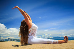 Blonde girl in lace sits on beach in yoga asana hands up Stock Photo