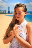 Blonde girl in lace sits in yoga asana thunderbolt on beach Stock Images