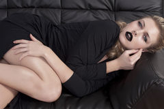 Blonde girl laying on a black sofa Royalty Free Stock Images