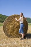 Blonde girl leaning against a rolling haystack. stock image