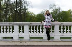 Blonde girl is leaning on railing Stock Photography