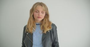 Blonde girl in leather jacket posing for camera being self-confident and cool isolated on white background. Blonde girl in leather jacket posing for camera stock footage