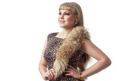 Blonde girl in leopard dress with fur on white background. Beautiful young blonde woman wearing a leopard dress with fur, isolated on a white background royalty free stock image