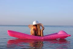 Blonde girl lie on the pink inflatable mattress on Red sea water stock photography