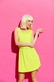Blonde girl in lime green dress pointing Royalty Free Stock Photography