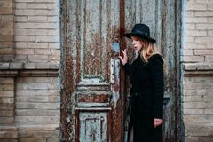 Blonde girl with long hair, in black coat in hat, stands on the background of vintage antique old wooden door old brick house. For stock image