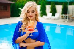Blonde girl with long hair holding cocktail and posing near pool on the sun royalty free stock photos