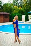 Blonde girl with long hair holding cocktail and posing near pool on the sun stock photography