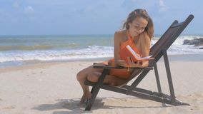 Blonde Girl Sits in Deck-chair with Diary on Beach stock footage