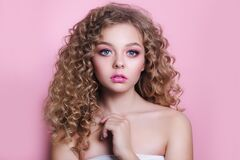 Blonde girl with long and shiny curly hair . Beautiful model woman with wavy hairstyle on pink background
