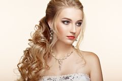 Blonde girl with long and shiny curly hair. Beautiful Model Woman with Curly Hairstyle. Care and Beauty Hair products. Perfect Make-Up and Jewelry Royalty Free Stock Photo