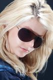 Blonde girl looking 02. Blonde girl looking, with a dark blue blouse and sunglasses, close-up Stock Images