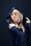 Blonde girl looking back. With a dark blue blouse and a hood on his head Stock Photos