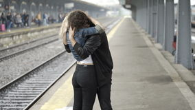 Blonde girl looking for boyfriend then kissing him and showing her love in train station. Cute blonde girl looking for boyfriend then kissing him and showing her stock video footage