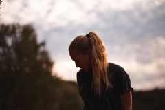 Blonde girl looking down. On sunset royalty free stock image