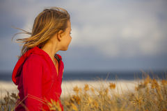 Blonde girl looking at the horizon. Young blond girl standing in grassland wearing a red hood and gazing at the horizon Stock Photo