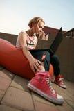 Blonde girl looking at laptop. Girl sitting down looking at laptop Royalty Free Stock Image