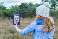 Blonde girl looking in mirror with forest background. Blonde caucasian teenage girl looking at mirror image with landscape background stock images