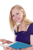 Blonde girl looking up from study book smiling Royalty Free Stock Photos