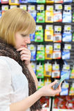 Blonde girl looks at battery in shop Royalty Free Stock Photography