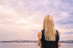 Blonde girl looks at the evening city near the river Stock Images