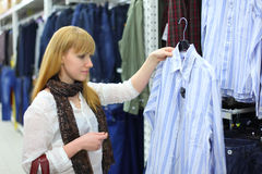 Blonde girl looks at male shirt in shop Royalty Free Stock Photo