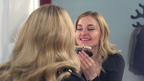 A blonde girl looks at the result front of the mirror of teeth whitening on a special color scale. The girl is happy