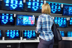 Blonde girl looks at TVs in supermarket Stock Photo
