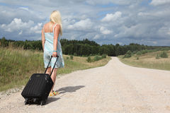 Blonde girl with luggage Stock Images
