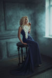 A blonde girl in a luxurious blue dress. With a long train. Gold make-up. Creative colors Stock Image