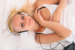 Blonde girl lying in bed listening to music Stock Image