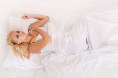 Blonde girl lying in bed Royalty Free Stock Photos