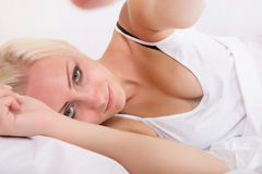 Blonde girl lying in bed reaching for someting Royalty Free Stock Photos