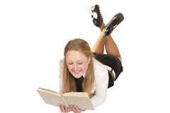 Blonde girl lying down reading a book Royalty Free Stock Image