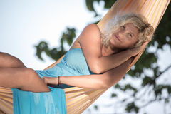 Blonde girl is lying in hammock Royalty Free Stock Photos