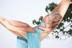 Blonde girl is lying in hammock Royalty Free Stock Photos