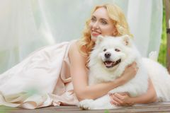 Blonde girl is lying outdoors with a white dog in hands. In a light dress Stock Image