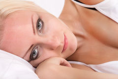 Blonde girl lying sideways in bed Royalty Free Stock Photography