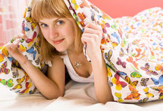 Blonde girl lying under a blanket with butterflies Royalty Free Stock Images