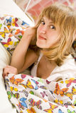 Blonde girl lying under a blanket with butterflies. Cute blonde girl lying on the bed under a blanket with butterflies Royalty Free Stock Photos