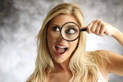 Blonde girl with a magnifying glass Royalty Free Stock Photo