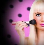 Blonde girl with make up brush Stock Image