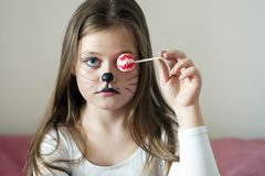 Blonde girl with a make-up imitating a cat holds in her hand a chupa chups. royalty free stock images