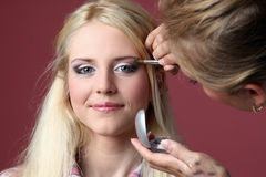 Blonde girl, make-up process Royalty Free Stock Photography