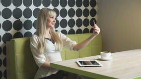 Blonde girl makes selfie using a grey mobile phone stock footage