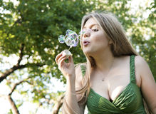 Blonde girl makes soap bubbles Royalty Free Stock Images